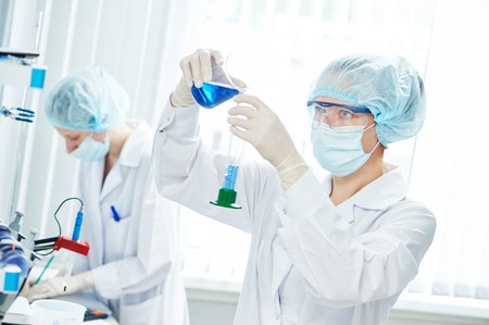 science laboratory work. female scientific researcher or doctor working with flask and blue liquid solution Stok Fotoğraf