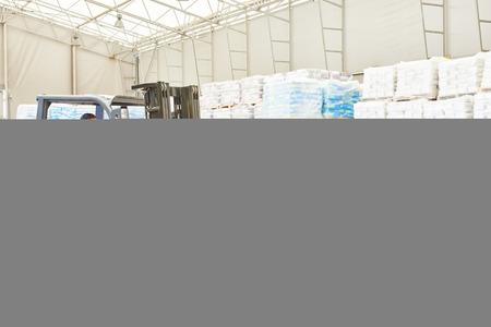 carretillas almacen: almacenaje. Conductor de la carretilla elevadora apilar palets con paquetes de cemento por cargador apilador