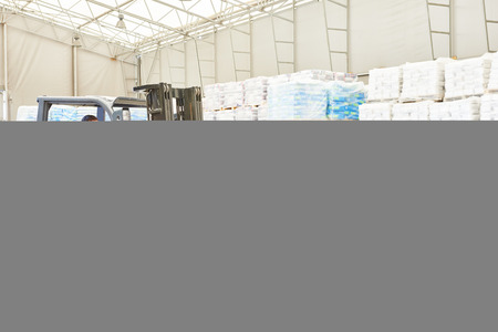 forklift driver: warehousing. Forklift driver stacking pallets with cement packs by stacker loader