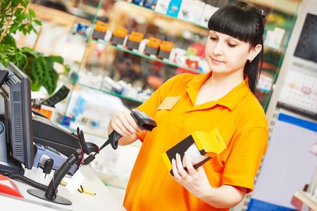 codigo de barras: vendedor femenino de la lámpara de exploración escáner de código de barras en la tienda Foto de archivo