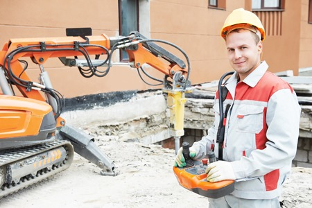 protective equipment: builder worker in safety protective equipment operating construction demolition machine robot Stock Photo
