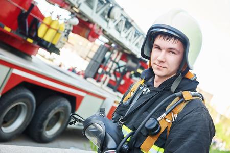 firefighter: bombero en uniforme frente a la m�quina de bomberos y el equipo de bombero