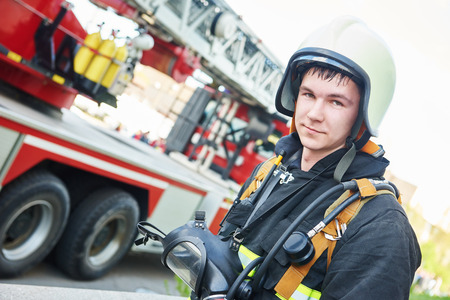 fireman: firefighter in uniform in front of fire engine machine and fireman team