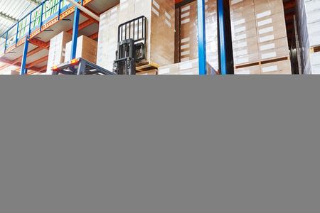 carretillas almacen: Programa piloto del trabajador del almacén en cardboxes apilamiento uniforme por cargador apilador carretilla elevadora