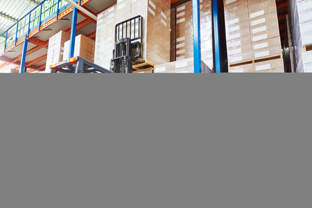 warehouse: warehouse worker driver in uniform stacking cardboxes by forklift stacker loader