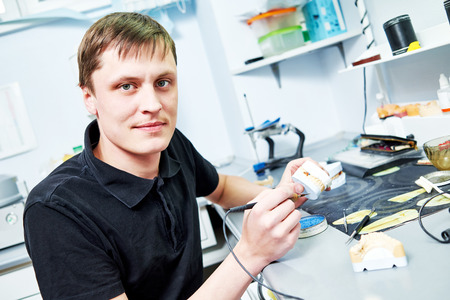 technologist: Dental technician working with tooth dentures at prosthesis laboratory
