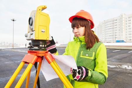 teodolito: trabajador agrimensor femenino que trabaja con equipos de tránsito teodolito en el sitio de construcción de la carretera al aire libre