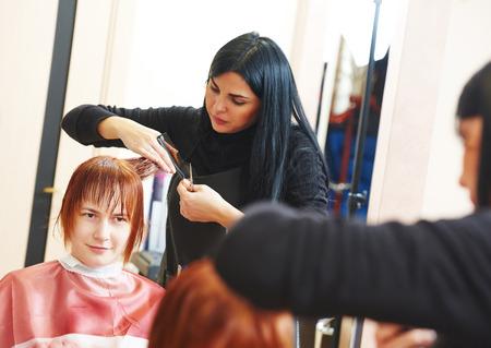 salon de belleza: Estilista de corte de pelo de un cliente femenino en el salón de belleza