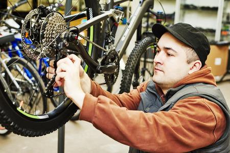 mecanico: Mantenimiento de bicicletas: mecánico reparador de militar de instalar el montaje o el ajuste de engranaje de la bicicleta en la rueda en el taller Foto de archivo