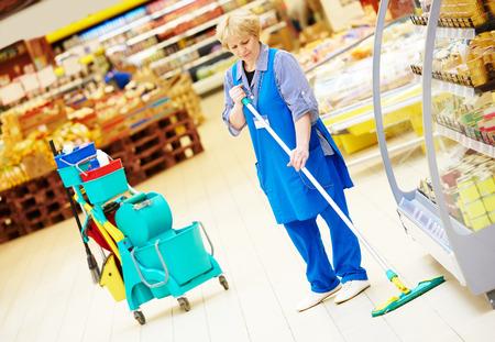 mojada: Servicios de cuidado y limpieza del piso con un trapeador en la tienda de supermercado tienda