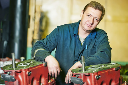 industrial worker assembler portrait with gearbox utits at manufacture workshop photo
