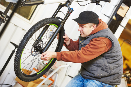 bicycle gear: Bike maintenance: mechanic serviceman repairman installing assembling or adjusting bicycle gear on wheel in workshop