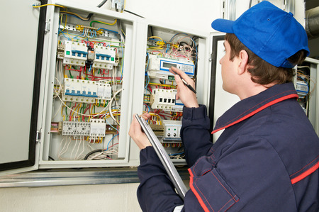 electrician builder engineer inspector checking data of equipment in fuse box photo