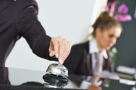 hotel staff: female receptionist worker ringing at hotel counter bell