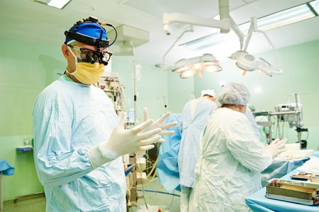 cardiosurgery: surgeons in uniform during heart transplantation operation on a patient at cardiac surgery clinic