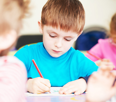 young boy: Cute little boy studying writing at the classroom