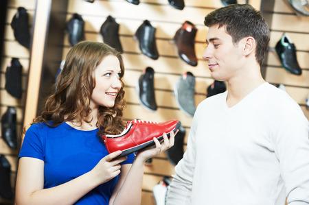 comprando zapatos: asistente femenina vendedor demostrar zapatos a joven durante las compras de calzado en la tienda de zapatos