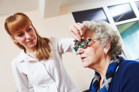 desease: Optometry. female doctor ophthalmologist or optometrist examines senior woman eye sight with phoropter in clinic