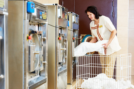 wash machine: cleaning services. Woman loading laundry washing machine with cloth