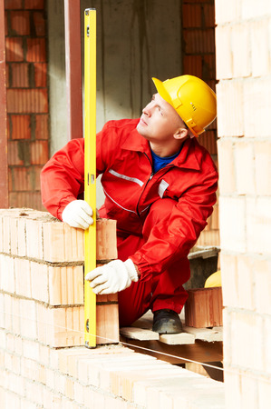 sand lime bricks: construction mason worker bricklayer making a brickwork with trowel and cement mortar