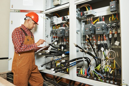electricidad industrial: trabajador ingeniero constructor electricista adulto con plan de esquema el�ctrico en frente de la Junta interruptor fusible