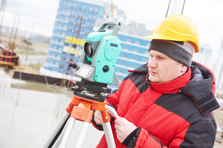 surveyor working with theodolite transit equipment at construction site photo