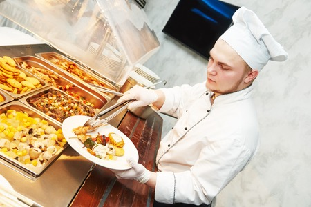 servings: Catering services. young cook chef serving food at buffet