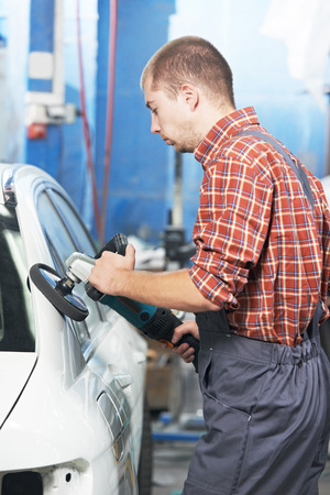 service station: auto mechanic worker polishing car body at automobile repair and renew service station shop by power buffer machine Stock Photo