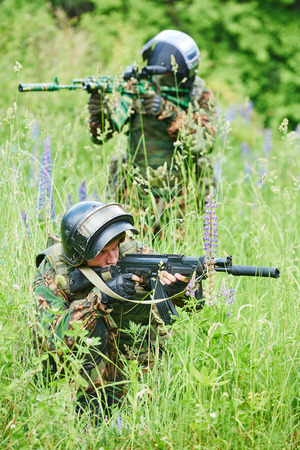 military. two soldier with assault rifle in uniform patrolling territory outdoors photo