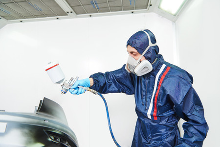 priming paint: worker  painting auto car bumper in a paint chamber during repair work
