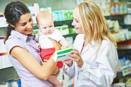 Mujer del químico farmacéutico dar vitaminas a la madre con el niño en droguería de la farmacia