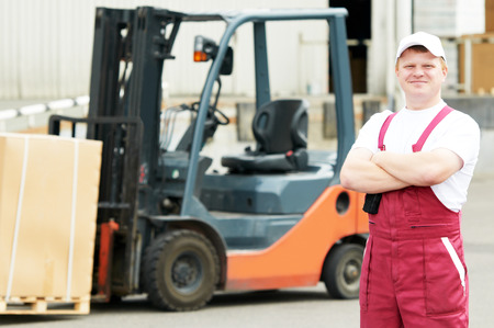 forklift driver: young warehouse worker portrait in uniform in front of modern storehouse forklift machine
