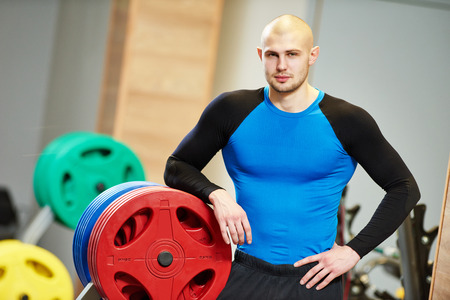 coaches: Portrait of a male fitness bodybuilder trainer coach standing in the gym
