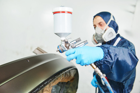 priming: worker  painting auto car bumper in a paint chamber during repair work