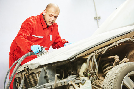 auto mechanic worker sanding polishing car at automobile repair and renew service station shop by sandpaper photo