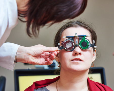 desease: Optometry concept. female doctor ophthalmologist or optometrist helps young woman with phoropter during sight testing or eye examinations in clinic
