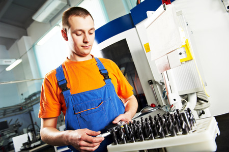 mechanical industrial worker measuring detail near metalwork machining center in tool manufacture workshop. Focus on labor face photo