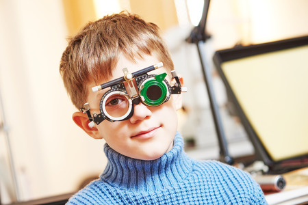 ophthalmology concept. young boy with phoropter during sight testing or eye examinations in clinic photo
