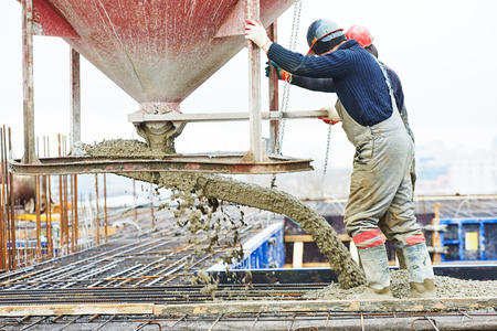 Hormigón: hormigonado de trabajo: sitio de construcción trabajador durante el vertido de hormigón en un encofrado en el área edificio con salto Foto de archivo