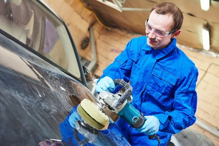 auto mechanic worker polishing car body at automobile repair and renew service station shop by power buffer machine 写真素材