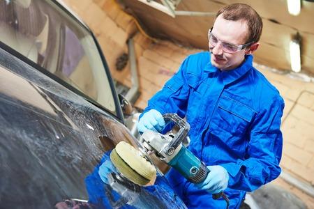 auto mechanic worker polishing car body at automobile repair and renew service station shop by power buffer machine Standard-Bild