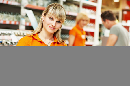 Positive female seller or shop assistant portrait  in hardware supermarket store 스톡 콘텐츠