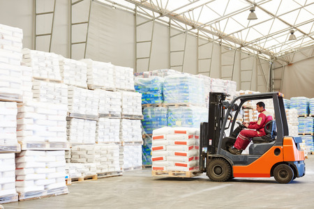 storage facility: warehousing. Forklift driver stacking pallets with cement packs by stacker loader