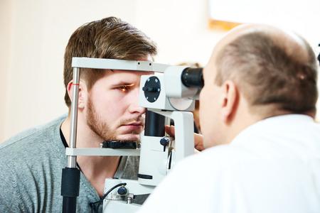 eyesight: Male optometrist optician doctor examines eyesight of female patient in eye ophthalmological clinic Stock Photo