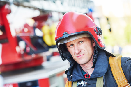 forcing: firefighter in uniform in front of fire engine machine and fireman team
