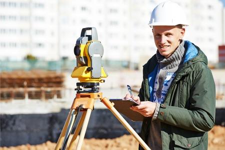teodolito: Trabajador constructor Top�grafo con equipos de tr�nsito teodolito en el sitio de construcci�n al aire libre durante el trabajo de agrimensura Foto de archivo