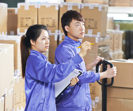 warehousing: two young chinese workers in uniform in discussing warehousing system