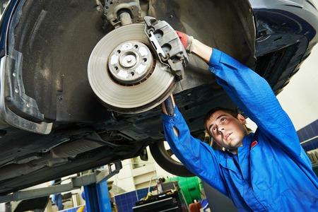 mecanico automotriz: mecánico de automóviles examinar rueda de disco y los zapatos de automóvil levantado freno del coche en la estación de servicio de reparación