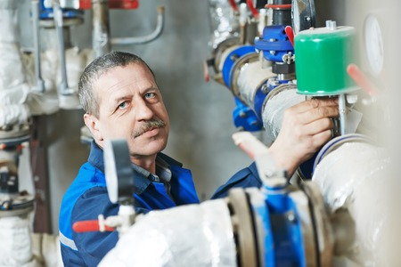 Industrial workers: repairman plumber engineer of fire engineering system or heating system open the valve equipment in a boiler house