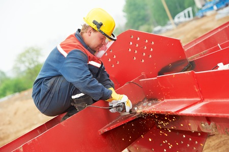 protective equipment: builder worker in safety protective equipment smothing out welded joint at metal construction frame by grinding machine Stock Photo